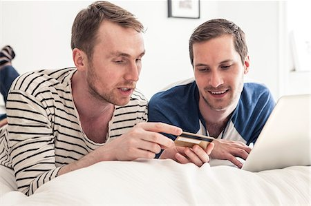 Homosexual couple shopping online on laptop together while lying in bed at home Stock Photo - Premium Royalty-Free, Code: 698-06966676