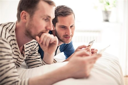 Homosexual couple looking at credit card while lying in bed at home Stock Photo - Premium Royalty-Free, Code: 698-06966678