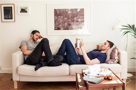 Young gay man reading book while partner looking at him on sofa Stock Photo - Premium Royalty-Free, Code: 698-06966670