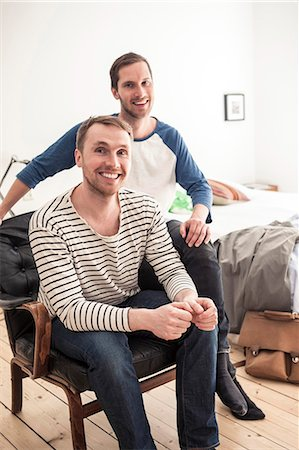 Portrait of happy homosexual couple sitting on chair in bedroom Stock Photo - Premium Royalty-Free, Code: 698-06966672