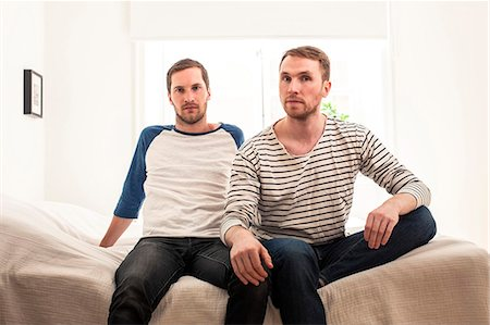 Portrait of homosexual couple sitting on bed at home Stock Photo - Premium Royalty-Free, Code: 698-06966673