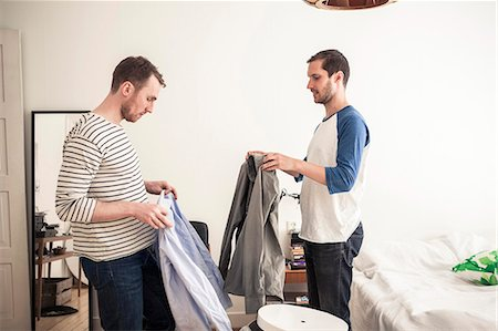 Side view of homosexual couple holding shirts in bedroom Stock Photo - Premium Royalty-Free, Code: 698-06966680
