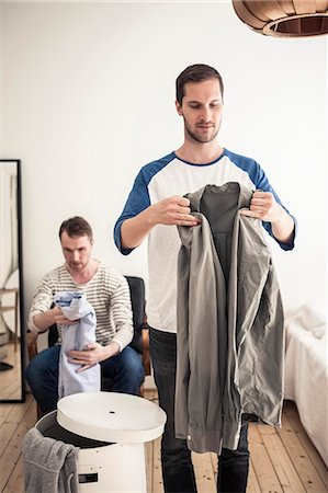 Gay men folding shirts in house Stock Photo - Premium Royalty-Free, Code: 698-06966681