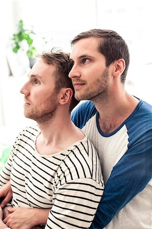 Thoughtful young homosexual couple looking away while embracing at home Stock Photo - Premium Royalty-Free, Code: 698-06966694