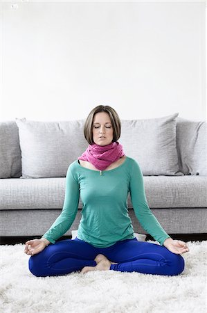 Front view of mid adult woman practicing yoga in living room Stock Photo - Premium Royalty-Free, Code: 698-06966737