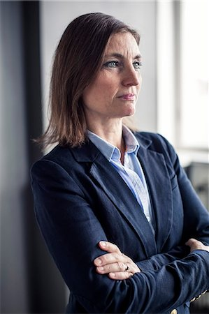 Thoughtful mature businesswoman looking away while standing arms crossed in office Stock Photo - Premium Royalty-Free, Code: 698-06966810