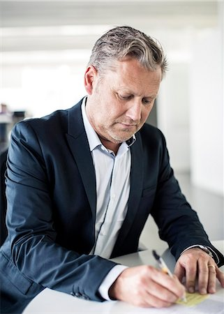 Mature businessman writing at desk in office Stock Photo - Premium Royalty-Free, Code: 698-06966829