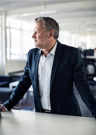 Thoughtful mature businessman looking away while standing at desk in office Stock Photo - Premium Royalty-Free, Code: 698-06966839