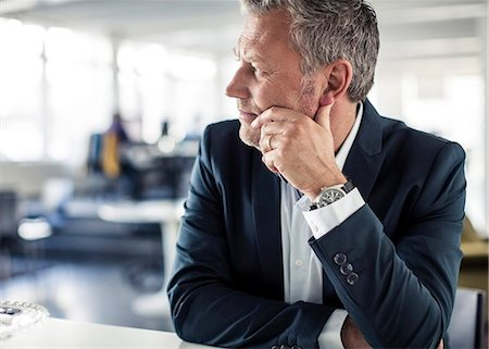 Thoughtful mature businessman looking away while sitting at desk in classroom Stock Photo - Premium Royalty-Free, Code: 698-06966840