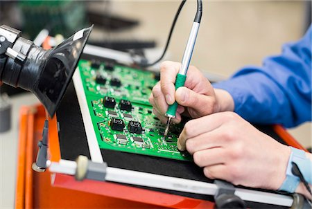 Cropped image of electrician's hand soldering circuit board Stock Photo - Premium Royalty-Free, Code: 698-06966855
