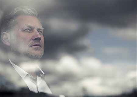 Reflection of clouds on glass window while businessman looking away Stock Photo - Premium Royalty-Free, Code: 698-06966853