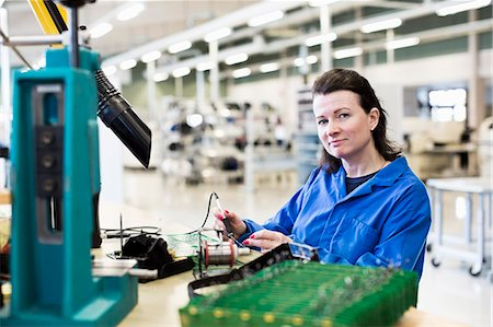 Portrait of confident female technician working on circuit board at desk in industry Stock Photo - Premium Royalty-Free, Code: 698-06966884