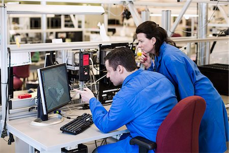 Male electrician pointing at computer monitor while discussing with colleague in industry Stock Photo - Premium Royalty-Free, Code: 698-06966890