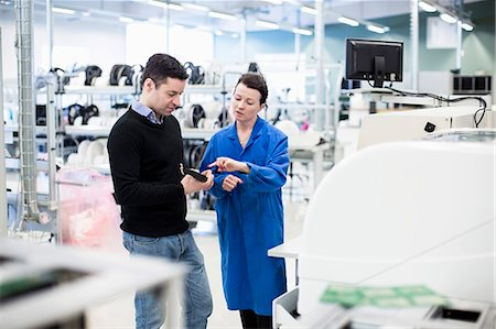 Mid adult female technician explaining machine part to client in factory Stock Photo - Premium Royalty-Free, Code: 698-06966902
