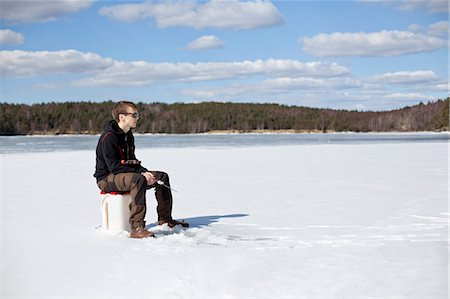 Young man ice fishing on frozen lake Stock Photo - Premium Royalty-Free, Code: 698-07158417
