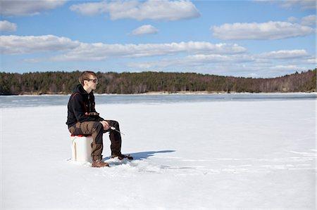 Young man ice fishing on frozen lake Stock Photo - Premium Royalty-Free, Code: 698-07158417