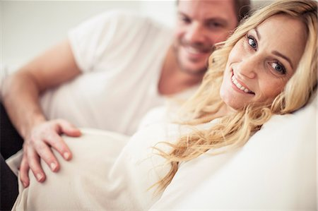 Portrait of happy pregnant woman with man lying in bed Stock Photo - Premium Royalty-Free, Code: 698-07158429