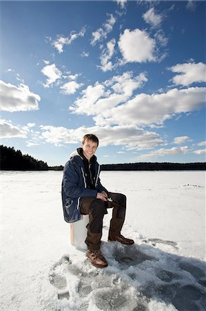 Portrait of happy young man ice fishing on frozen lake Stock Photo - Premium Royalty-Free, Code: 698-07158421