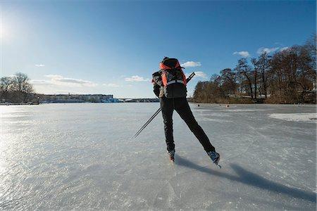 Rear view of man skating on frozen lake Stock Photo - Premium Royalty-Free, Code: 698-07158450