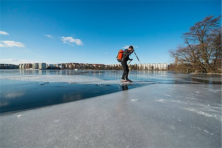 Full length of man skating on frozen lake Stock Photo - Premium Royalty-Free, Code: 698-07158451