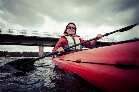 Happy mature woman paddling kayak on river with bridge in background Stock Photo - Premium Royalty-Free, Code: 698-07158470