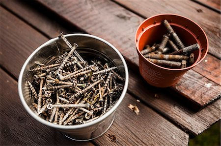 Containers of rusty nails on wooden table Stock Photo - Premium Royalty-Free, Code: 698-07158471