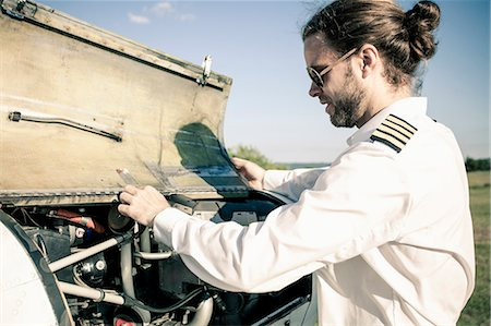 Side view of pilot checking oil in propeller aeroplane Stock Photo - Premium Royalty-Free, Code: 698-07158499