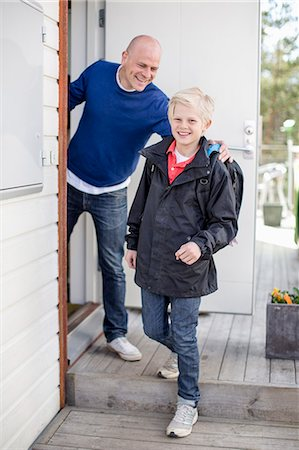 Portrait of happy boy leaving for school while father looking at him Stock Photo - Premium Royalty-Free, Code: 698-07158534