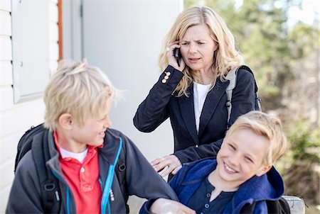 Irritated mother using mobile phone while stopping mischievous sons Stock Photo - Premium Royalty-Free, Code: 698-07158544