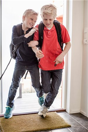 Boys pushing each other while entering home from school Stock Photo - Premium Royalty-Free, Code: 698-07158541