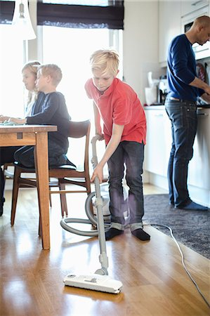 Boy vacuuming hardwood floor with family in background Stock Photo - Premium Royalty-Free, Code: 698-07158554
