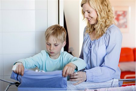 Smiling mother looking at son drying laundry on rack Stock Photo - Premium Royalty-Free, Code: 698-07158566