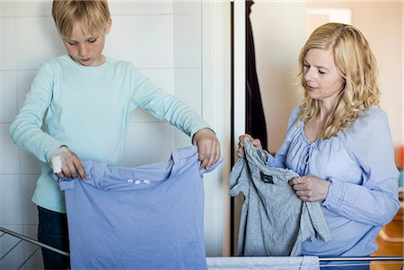 Mother and son drying laundry on rack at home Stock Photo - Premium Royalty-Free, Code: 698-07158567
