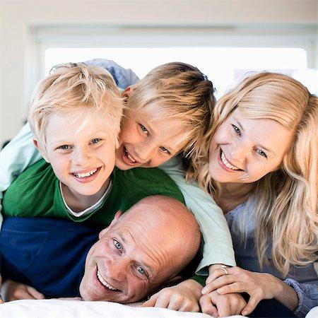 Portrait of happy family enjoying in bed Stock Photo - Premium Royalty-Free, Code: 698-07158569