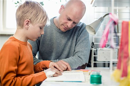 Father helping son with homework at table Stock Photo - Premium Royalty-Free, Code: 698-07158561