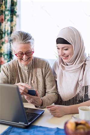 Senior woman with female home caregiver visiting bank through laptop at home Stock Photo - Premium Royalty-Free, Code: 698-07158586
