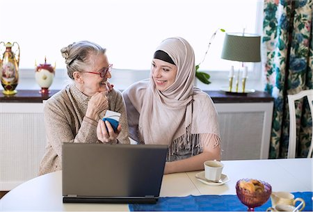 Happy young female home caregiver with senior woman doing bank transaction on laptop Stock Photo - Premium Royalty-Free, Code: 698-07158588