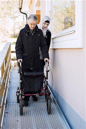 Female home caregiver helping senior woman with walking frame through passage Stock Photo - Premium Royalty-Free, Code: 698-07158609