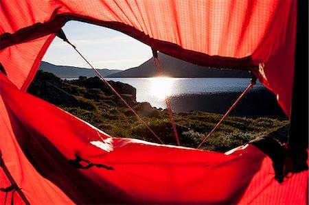 View of sunlight reflecting on lake through tent Stock Photo - Premium Royalty-Free, Code: 698-07158628