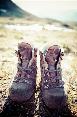 Pair of dirty hiking boots on land Stock Photo - Premium Royalty-Free, Code: 698-07158621