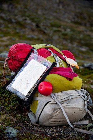 Hiking backpack with sleeping bag and map in forest Stock Photo - Premium Royalty-Free, Code: 698-07158623