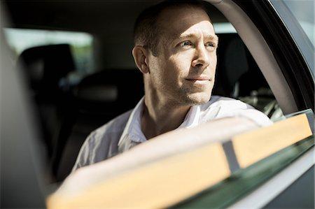 Businessman looking through taxi window Stock Photo - Premium Royalty-Free, Code: 698-07158636