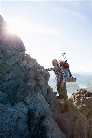Portrait of happy female climber standing on rocks against sky Stock Photo - Premium Royalty-Free, Code: 698-07158632