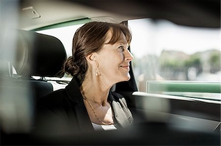 Businesswoman looking out through taxi window Stock Photo - Premium Royalty-Free, Code: 698-07158644