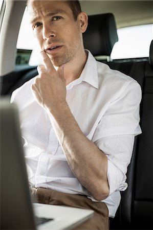 Thoughtful businessman with laptop sitting in taxi Stock Photo - Premium Royalty-Free, Code: 698-07158647