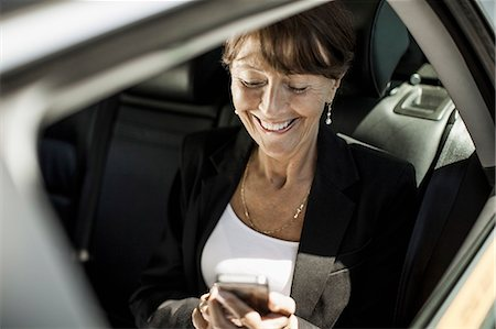 Happy businesswoman using mobile phone in taxi Stock Photo - Premium Royalty-Free, Code: 698-07158641