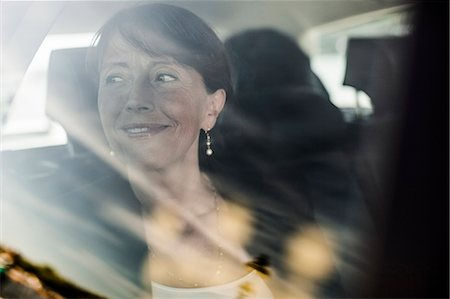 View of businesswoman smiling while looking out through taxi window Stock Photo - Premium Royalty-Free, Code: 698-07158650