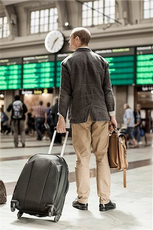 Businessman with luggage standing on railway station Stock Photo - Premium Royalty-Free, Code: 698-07158653