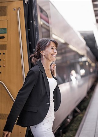 Happy businesswoman disembarking train Stock Photo - Premium Royalty-Free, Code: 698-07158664