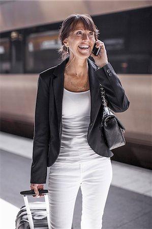 Happy businesswoman using mobile phone on railroad station platform Stock Photo - Premium Royalty-Free, Code: 698-07158665